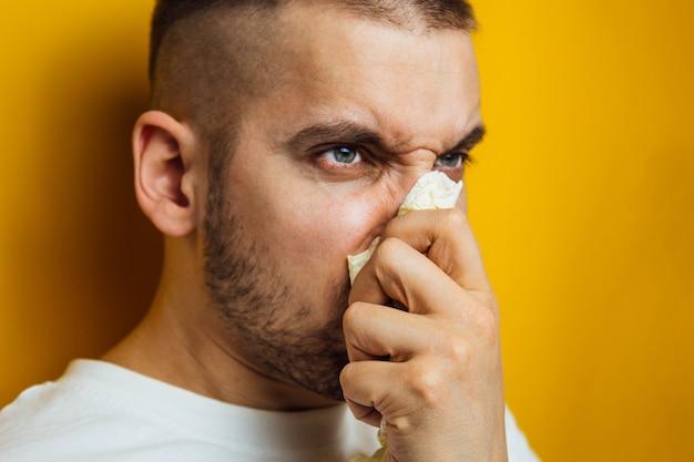 Junger mann mit einem virus niest in toilettenpapier, das er in seinen händen hält. allergiesaison, pandemie, erkältungen. unzufriedener gesichtsausdruck.