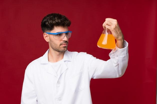 Junger mann mit einem wissenschaftlichen reagenzglas
