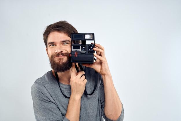 Junger mann mit einer alten kamera auf einer hellen wand