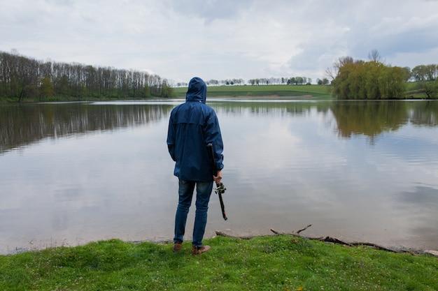 Junger mann mit einer angelrute, die auf dem see steht