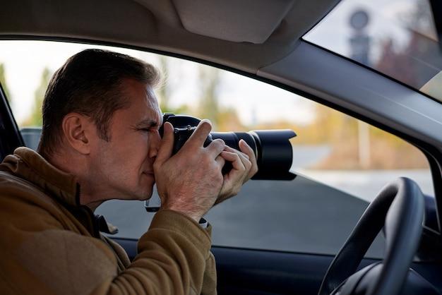Junger mann mit einer dslr-kamera in einem auto