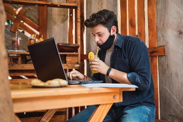 Junger mann mit einer gesichtsmaske, die ein glas saft an einer bar trinkt.