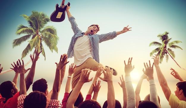 Junger mann mit einer gitarre, die auf einem strand-konzert durchführt