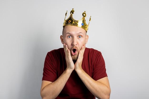 Junger mann mit einer krone auf dem kopf isoliert