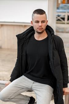 Junger mann mit einer kurzen frisur in einer schwarzen winterjacke in weißen jeans sitzt auf der straße