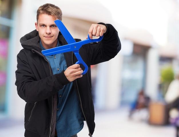 Junger mann mit einer schere