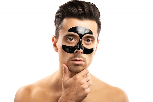Junger mann mit einer schwarzen kohlemaske auf seinem gesicht auf weiß.