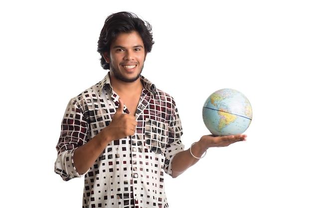 Junger mann mit einer weltkugel auf einem weiß.