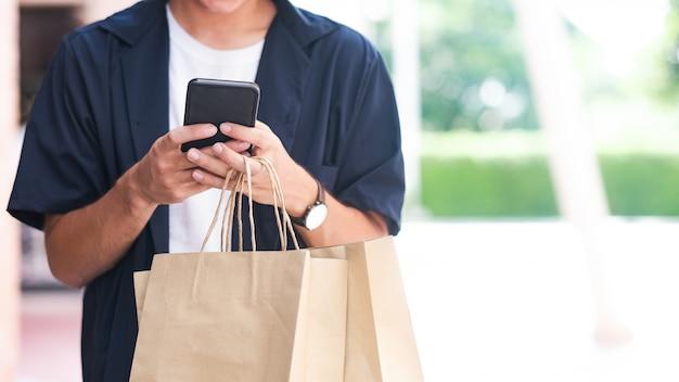 Junger mann mit einkaufstaschen benutzt einen handy beim einkaufen