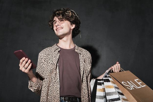 Junger mann mit einkaufstüten mit handy für online-shopping auf schwarzem hintergrund isoliert