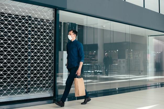 Junger mann mit einkaufstüten zu fuß entlang einer stadtstraße. coronavirus in der stadt