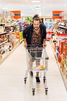 Junger mann mit einkaufswagen im supermarkt
