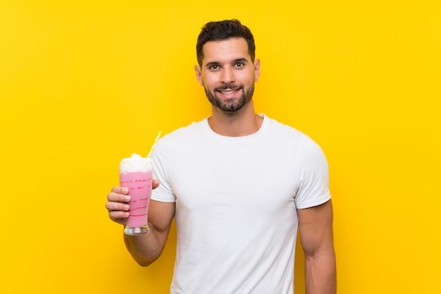 Junger mann mit erdbeermilchshake über lokalisierter gelber wand viel lächelnd