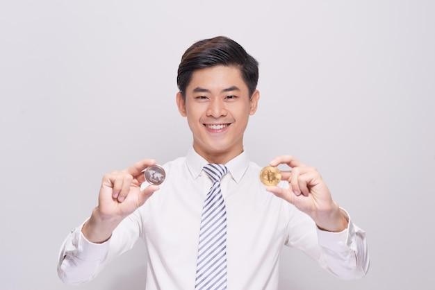 Junger mann mit ethereumac und bitcoin auf weißem hintergrund