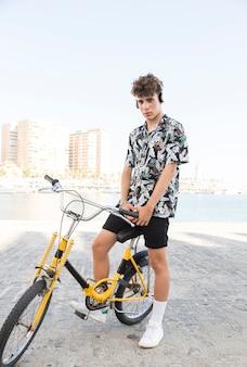 Junger mann mit fahrrad hörend musik auf kopfhörer