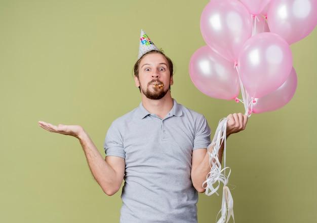 Junger mann mit feiertagskappe, die ballons hält, die verwirrte feiernde geburtstagsfeier stehen über heller wand halten