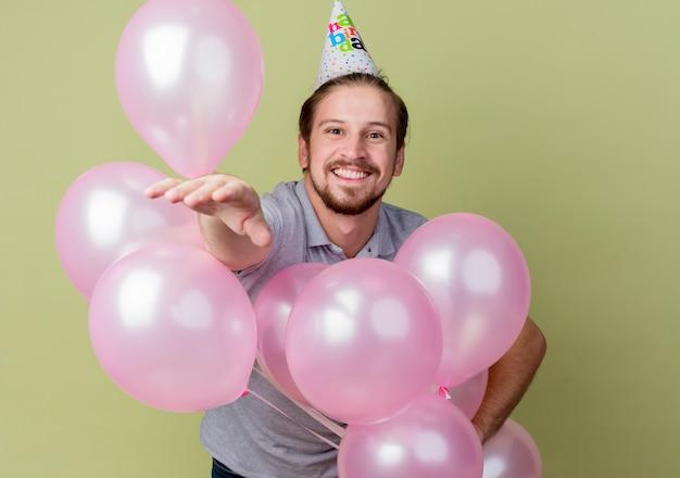 Junger mann mit feiertagsmütze, die geburtstagsfeier feiert, die ballons chappy und aufgeregtes lächelndes fröhliches stehen über lichtwand hält
