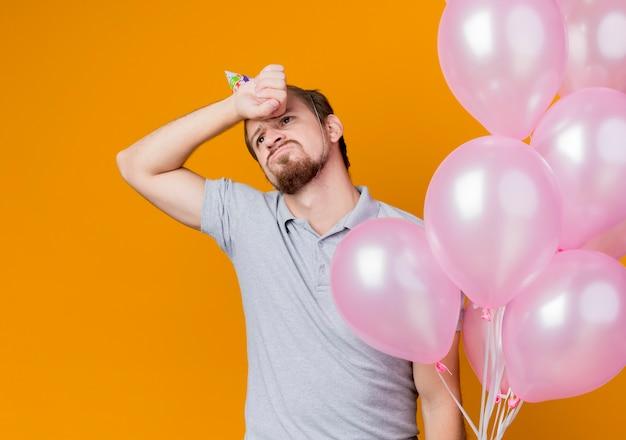 Junger mann mit feiertagsmütze, die geburtstagsfeier feiert, die bündel der luftballons hält, die unzufrieden müde und gelangweilt stehen über orange wand schauen