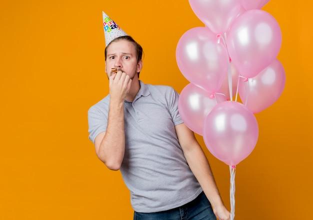Junger mann mit feiertagsmütze, die geburtstagsfeier feiert, die bündel der luftballons über orange überrascht