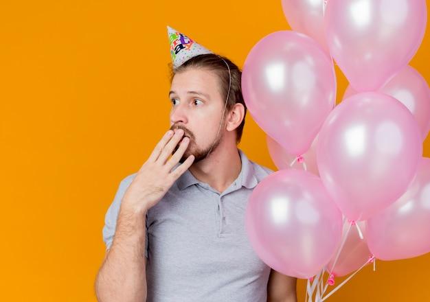 Junger mann mit feiertagsmütze, die geburtstagsfeier feiert, die bündel von luftballons hält, die beiseite schauen mund mit hand überrascht und über orange erstaunt
