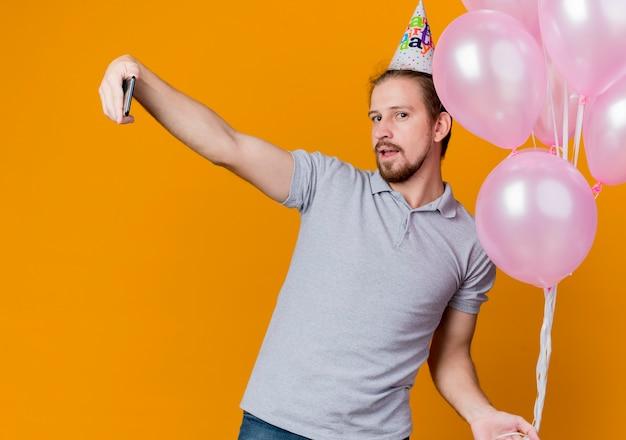 Junger mann mit feiertagsmütze, die geburtstagsfeier feiert, die bündel von luftballons tut, die selfie unter verwendung des smartphones stehen, das über orange wand steht