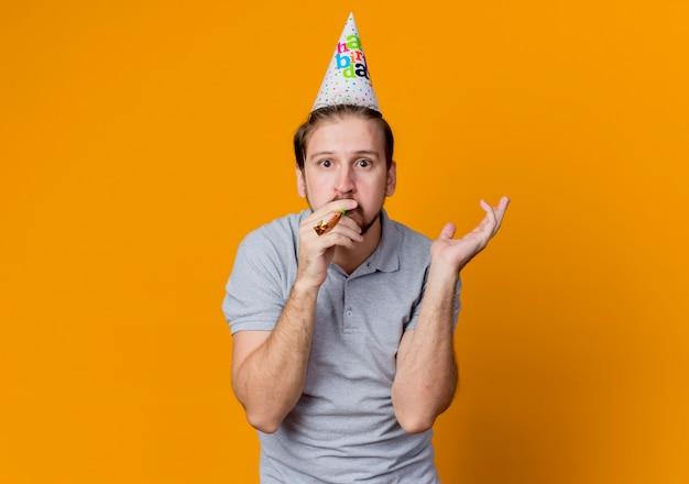 Junger mann mit feiertagsmütze, die geburtstagsfeier feiert, die urprised steht über orange wand steht