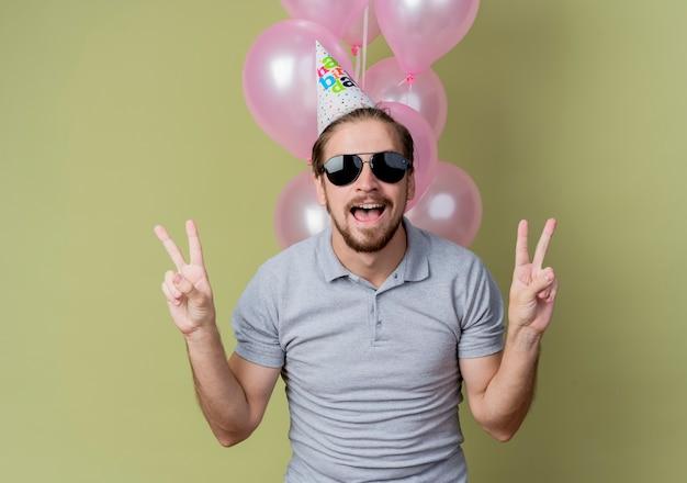 Junger mann mit feiertagsmütze, die geburtstagsfeier feiert, die verrückte glückliche und aufgeregte lächelnde luftballons hält, die fröhlich v-zeichen zeigen, das über lichtwand steht