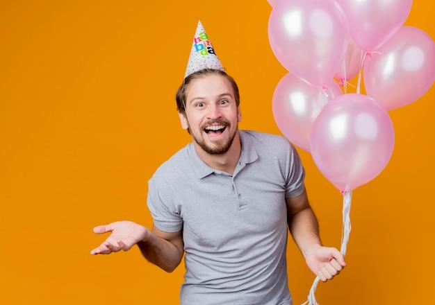 Junger mann mit feiertagsmütze, die geburtstagsfeier hält, die ballons hält, die fröhlich mit arm herausstehen, der über orange wand steht