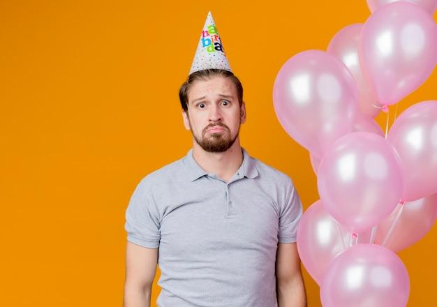 Junger mann mit feiertagsmütze, die geburtstagsfeier hält, die ballons mit traurigem ausdruck auf gesicht steht, das über orange wand steht