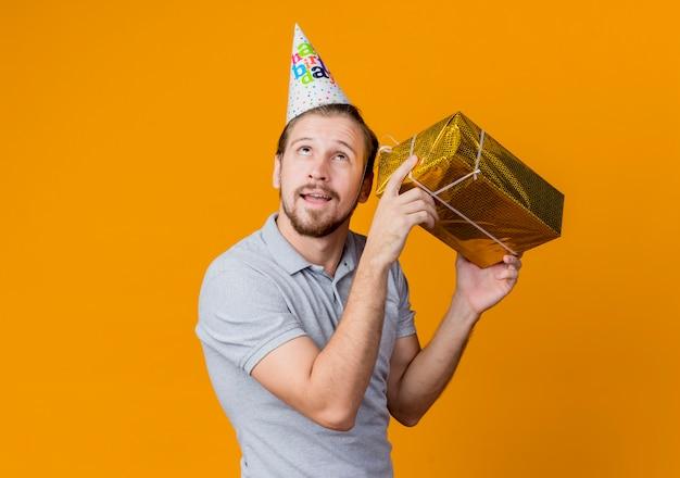 Junger mann mit feiertagsmütze feiert geburtstagsfeier, die geschenkbox nahe seinem ohr mit nachdenklichem ausdruck hält, der über orange wand steht