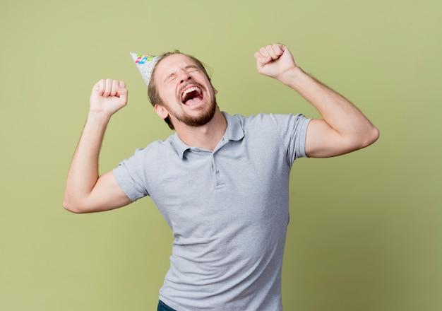 Junger mann mit feiertagsmütze feiert geburtstagsfeier verrückt glücklich und aufgeregt über lichtwand
