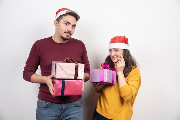 Junger mann mit frau, die mit weihnachtsgeschenken aufwirft.