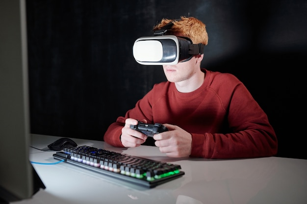 Junger mann mit gamepad im vr-headset, das vor computerbildschirm sitzt, während virtuelle spiele in der dunkelheit spielt