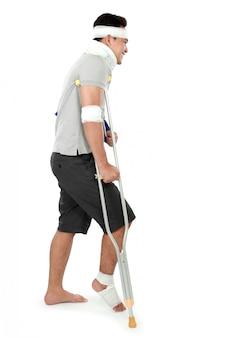 Junger mann mit gebrochenem bein auf krücke