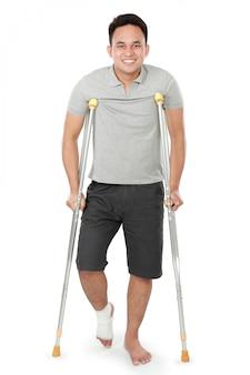 Junger mann mit gebrochenem bein benutzen krücken