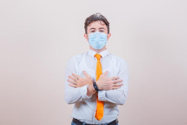 Junger mann mit gekreuzten händen auf der brust in hemd, krawatte, jeans, maske
