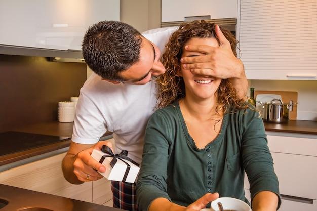 Junger mann mit geschenkbox, der die augen seiner freundin für eine überraschung schließt, während er in der heimischen küche frühstückt