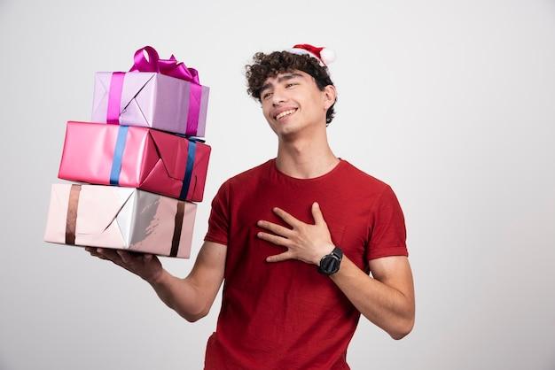 Junger mann mit geschenkboxen, der sich zufrieden fühlt