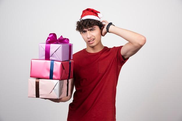 Junger mann mit geschenkboxen, die kopfschmerzen haben.