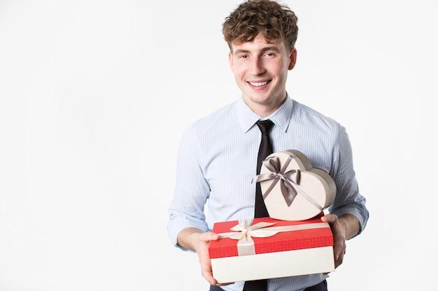 Junger mann mit geschenken in den händen auf einem weißen hintergrund.