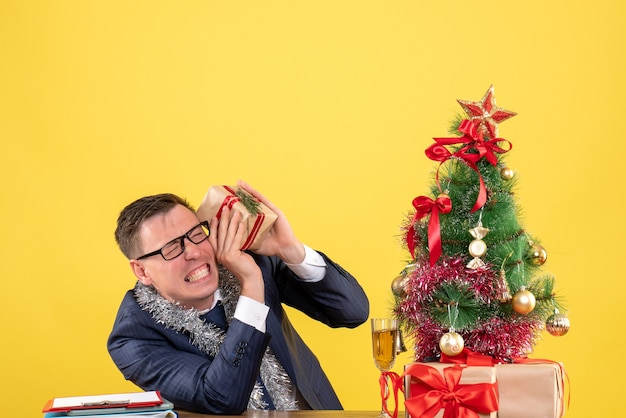 Junger mann mit geschlossenen augen, die geschenk halten, das am tisch nahe weihnachtsbaum und geschenken auf gelb sitzt