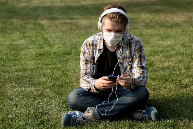 Junger mann mit gesichtsmaske, die musik hört
