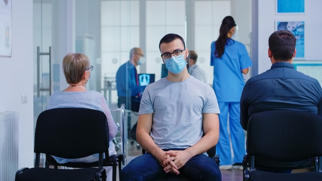 Junger mann mit gesichtsmaske gegen coronavirus mit blick auf die kamera im wartebereich des krankenhauses. ältere frau mit gehrahmen, die auf beratung in der klinik wartet.