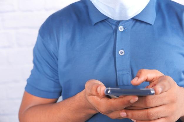 Junger mann mit gesichtsmaske unter verwendung des innenraums des smartphones