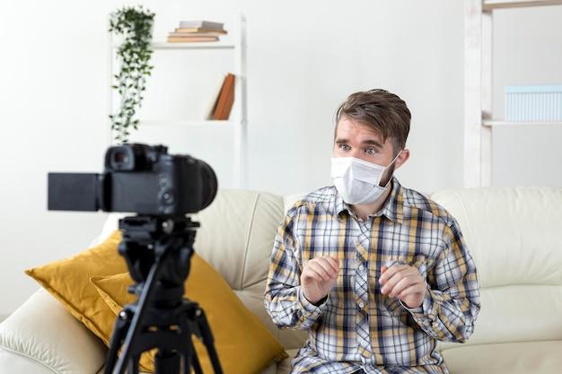 Junger mann mit gesichtsmaskenaufzeichnungsvideo zu hause