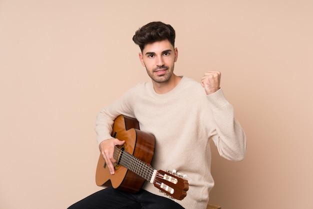 Junger mann mit gitarre einen sieg feiernd