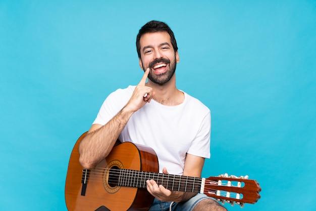 Junger mann mit gitarre lächelnd mit einem glücklichen und angenehmen ausdruck