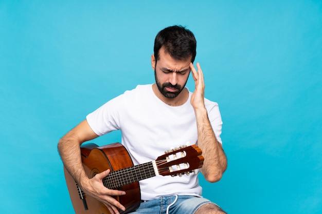 Junger mann mit gitarre mit kopfschmerzen