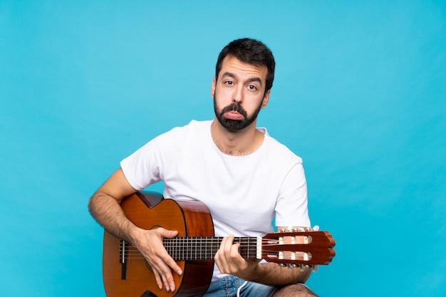 Junger mann mit gitarre mit traurigem und deprimiertem ausdruck