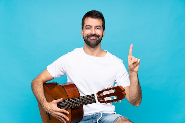 Junger mann mit gitarre über dem lokalisierten blau, das einen finger im zeichen des besten zeigt und anhebt